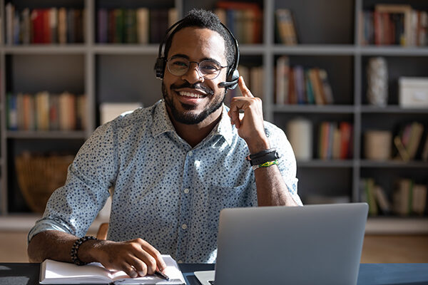Happy young african american man wearing headset, looking at camera.